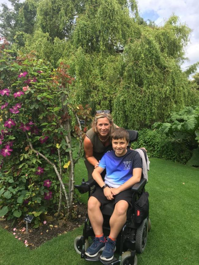 Mother and son - disabled George, 11, who relies on his wheelchair, with his mother Kerry, in the garden of their home in Billericay