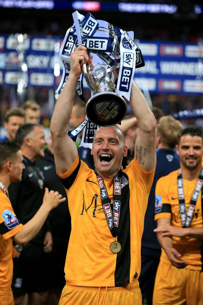 Celebration time - Adam Barrett holds aloft the League Two play-off winning trophy