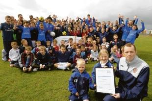 Award time — Essex County FA club development officer Ian Bent and Kyle Williams, five, and Rebecca Ashley, seven, with the FA Charter Standard Develop-ment status award bestowed on Forest Glade
