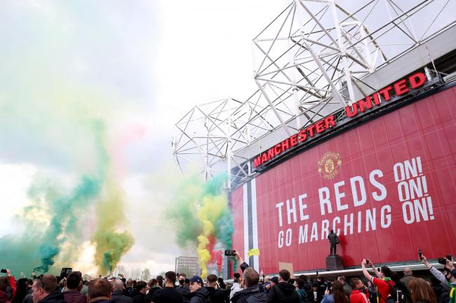 Fans let off flares as they protested against the Glazer family