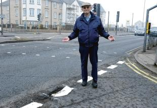 Barry Fountain says the council is wasting money painting over potholes