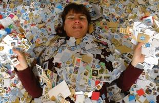 A welcome stamp of approval – Terri covered in some of the postage stamps she selflessly sifts through and sorts out