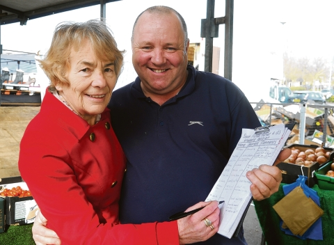 Signing the petition – customer Breda Green gives trader Thomas Tuohy her support