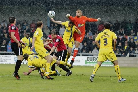 My ball - Torquay goalkeeper Robert Olejnik punches clear under pressure