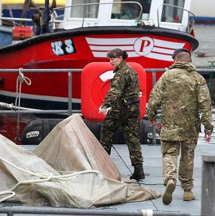 RAF personnel view Tornado plane wreckage covered by a tarpaulin at Buckie Lifeboat station