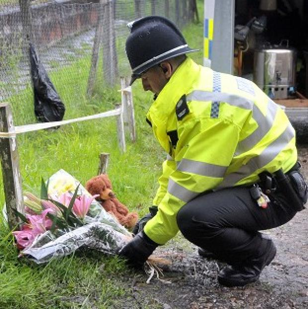 A police officer lays floral tributes to three children who detectives confirmed were stabbed to death