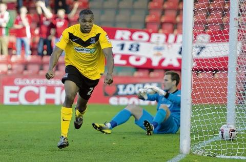 Britt Assombalonga celebrates his goal at Cheltenham Town