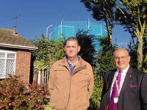 Cage in their midst – councillor Brian Wood and resident Martin Kingsland outside the bungalows, with the sports cage clearly in view beyond
