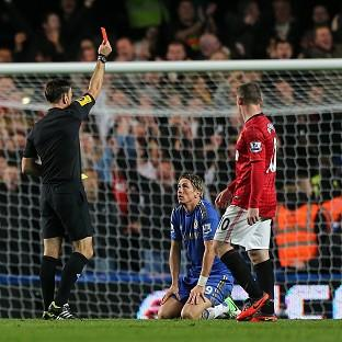 Referee Mark Clattenburg shows a red card to Chelsea's Fernando Torres