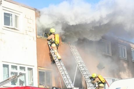 Firefighters at the scene of the blaze this morning - the fire was still smouldering at 4pm