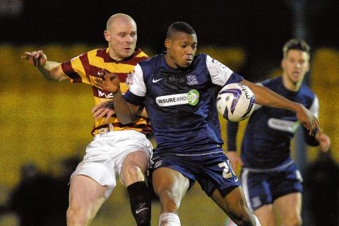 Behind you - Britt Assombalonga under pressure from Bradford's Gary Jones