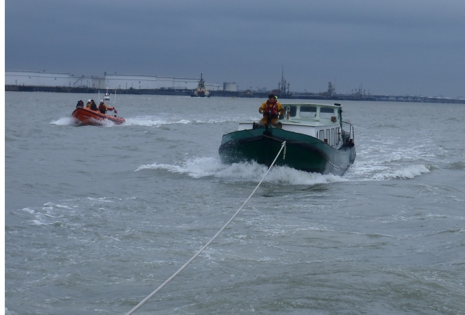 The burnt out vessel is pulled to shore by the Sheerness RNLI boat