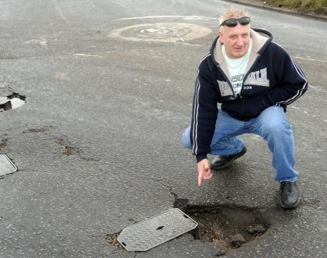 Kevin Attridge points to the pothole