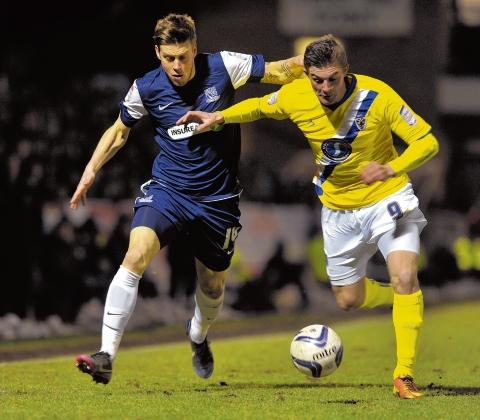 Kevan Hurst battles for the ball with AFC Wimbledon's Ben Dickenson