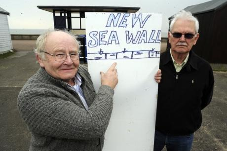 Anti-seawall campaigners Peter Grubb and Ray Bailey near Uncle Tom's Cabin, Shoebury Common Road, Shoebury, demonstrating the height of the proposed embankment