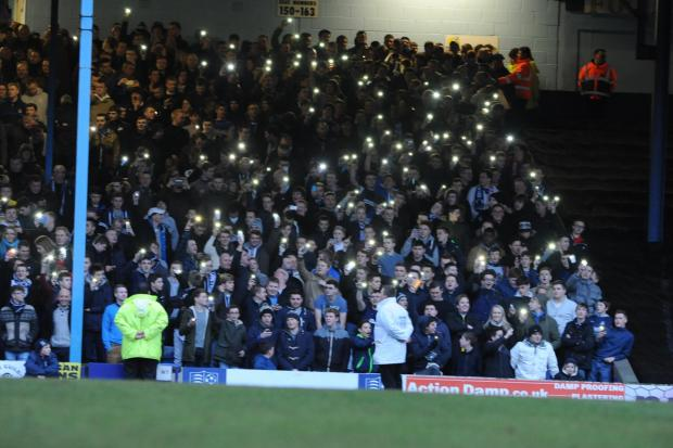 Southend United's fans shine their mobile phones towards the pitch after the floodlights went out at Roots Hall