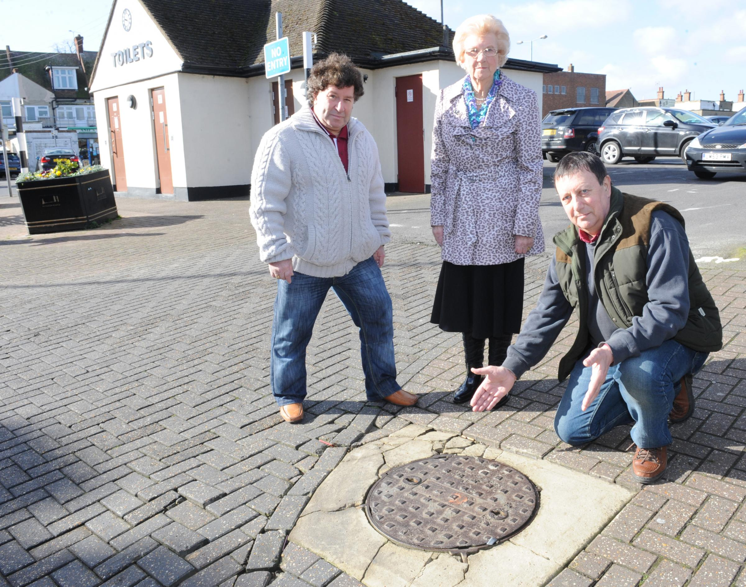 Who is to blame? Tory Norman Ladzrie kneels beside the manhole with councillor Godfrey Isaacs and Heather Overall, who was injured by it last year