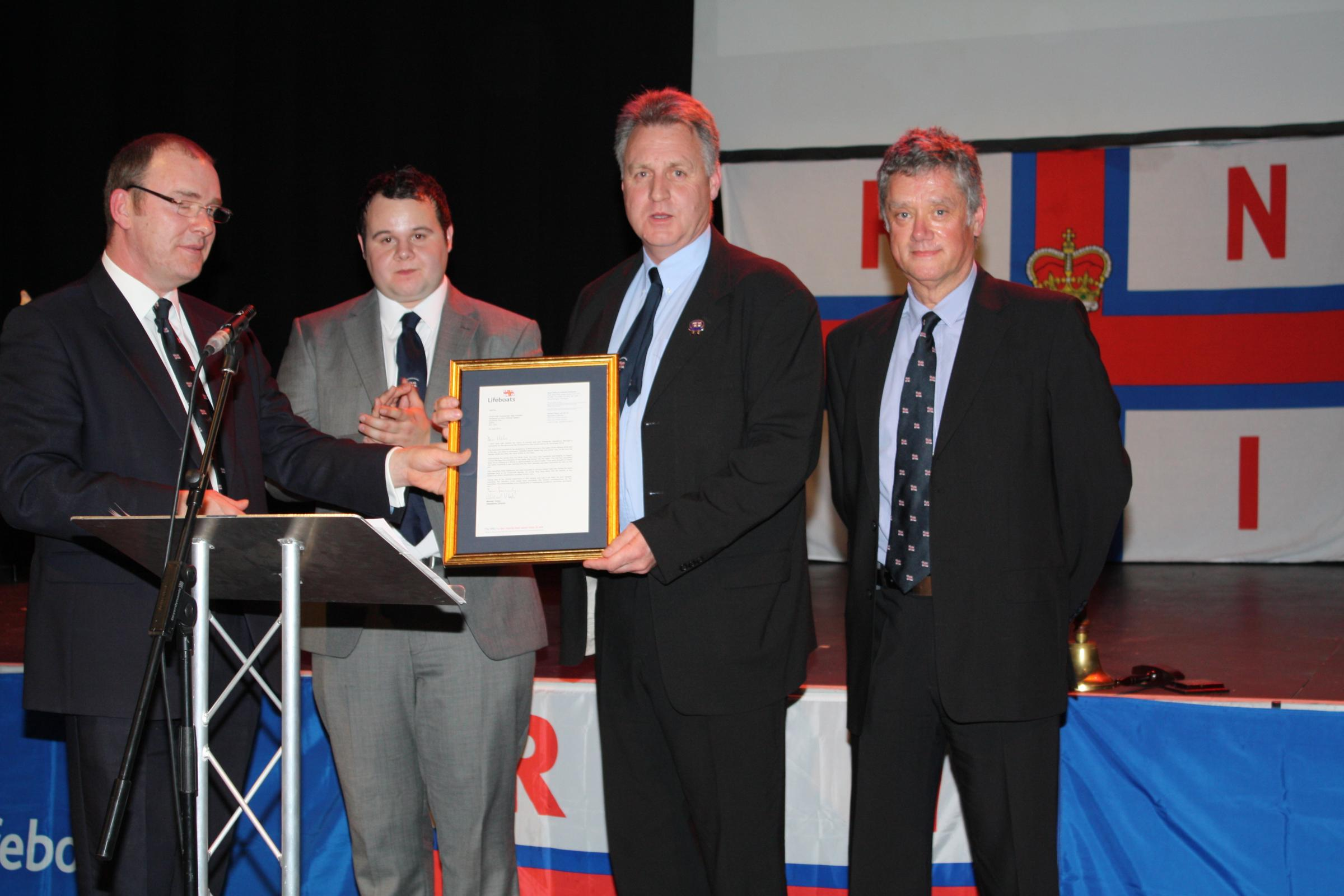 Commended - RNLI official David Shepherd presents the letter to Michael Whistler, Adam Manning and Dave Brown