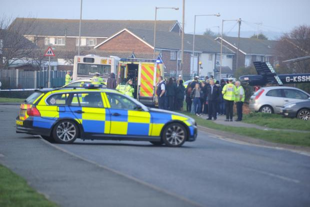 Residents watch on as police, paramedics and air ambulance crews surround the bus