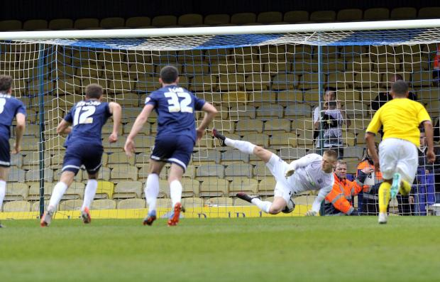 Jack Midson's penalty squirms under the body of Southend United goalkeeper Daniel Bentley