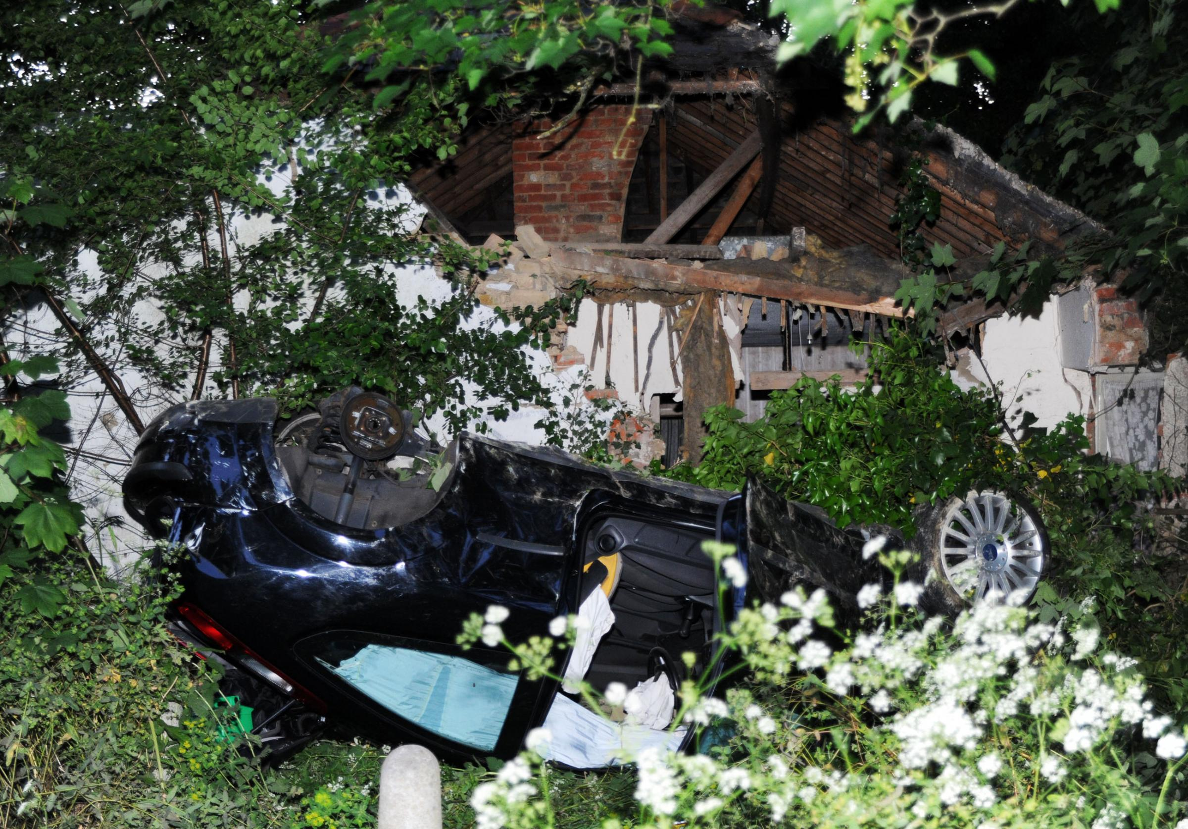 Car involved in police chase flips upside down hits bungalow - and driver gets away