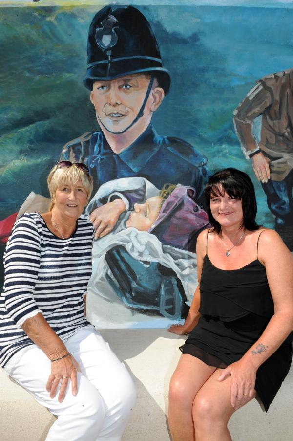 Judy Dolby who is the little girl in the picture being carried by PC Bobby Pilgrim with artist Sue Pattle who painted this part of the mural
