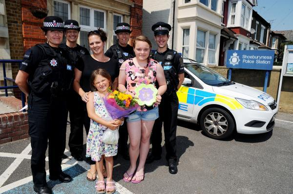 Our heroes – Clare Palmer and her daughters Chelsea, 11, and Leah, six, present flowers to Sgt Tracey Butt and PCs Nikki Cornish, Sharon Blaxland and David Gardiner