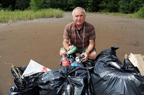Angry – councillor Dave Blackwell with some of the rubbish collected after Sunday's illegal rave at the nature reserve