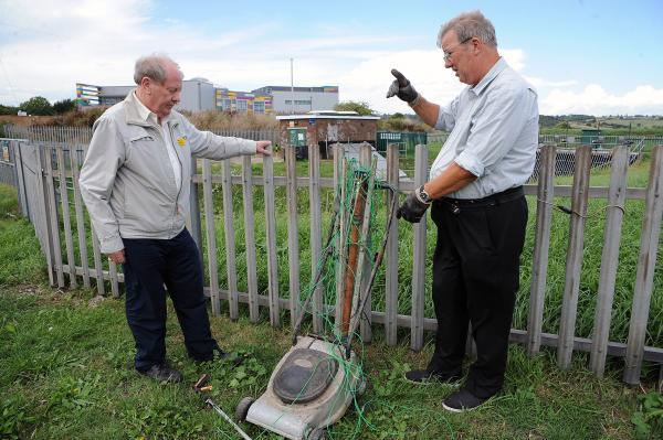Clean-up – councillor Ray Howard, left, and Colin Letchford with a lawnmower dragge
