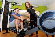 Daniel Brooks on the rowing machine at Club Kingswood as fitness instructor Louise Basham passes on some tips