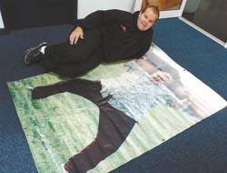New man - Jody beside a life-size picture of him at 31 stone