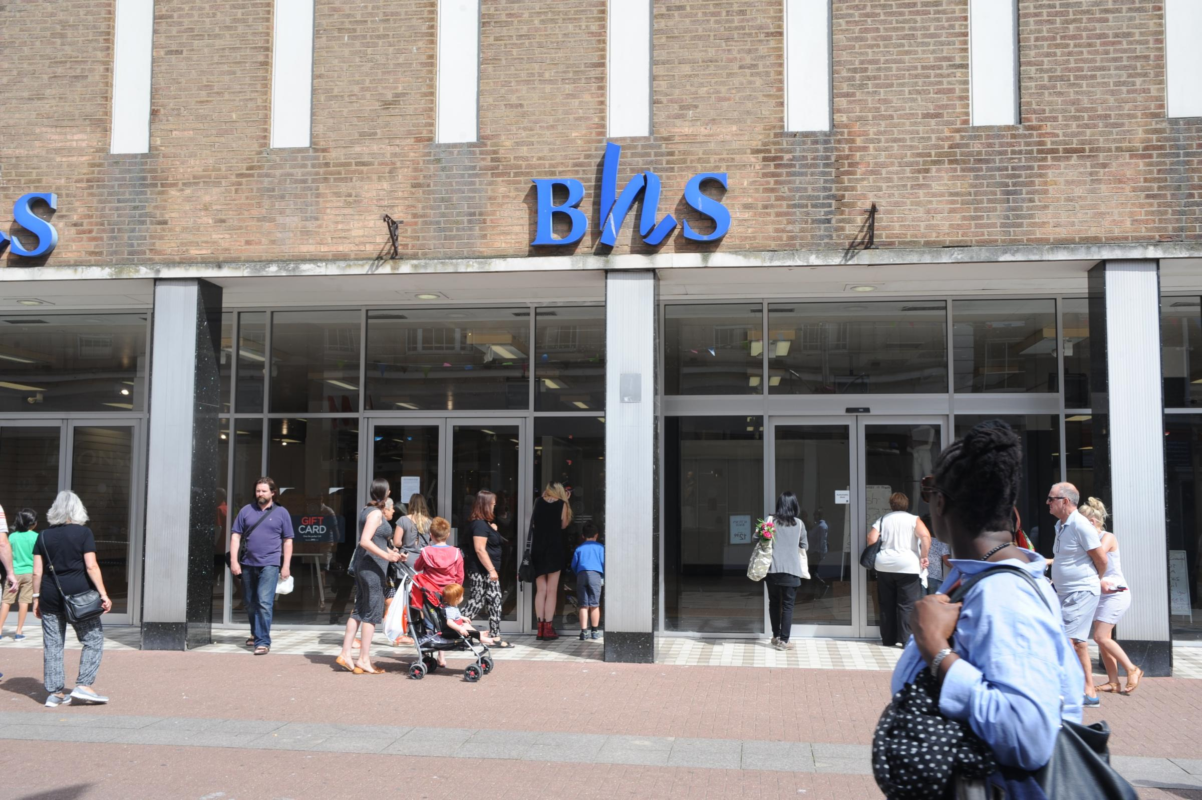 Bemused shoppers peer at signs put up by squatters who have moved into the newly empty BHS store.