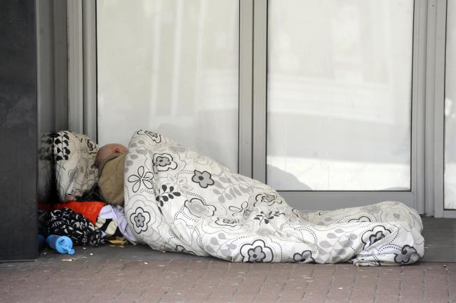 In the cold - homeless person sleeping rough in doorway of empty shop in Southend High Street