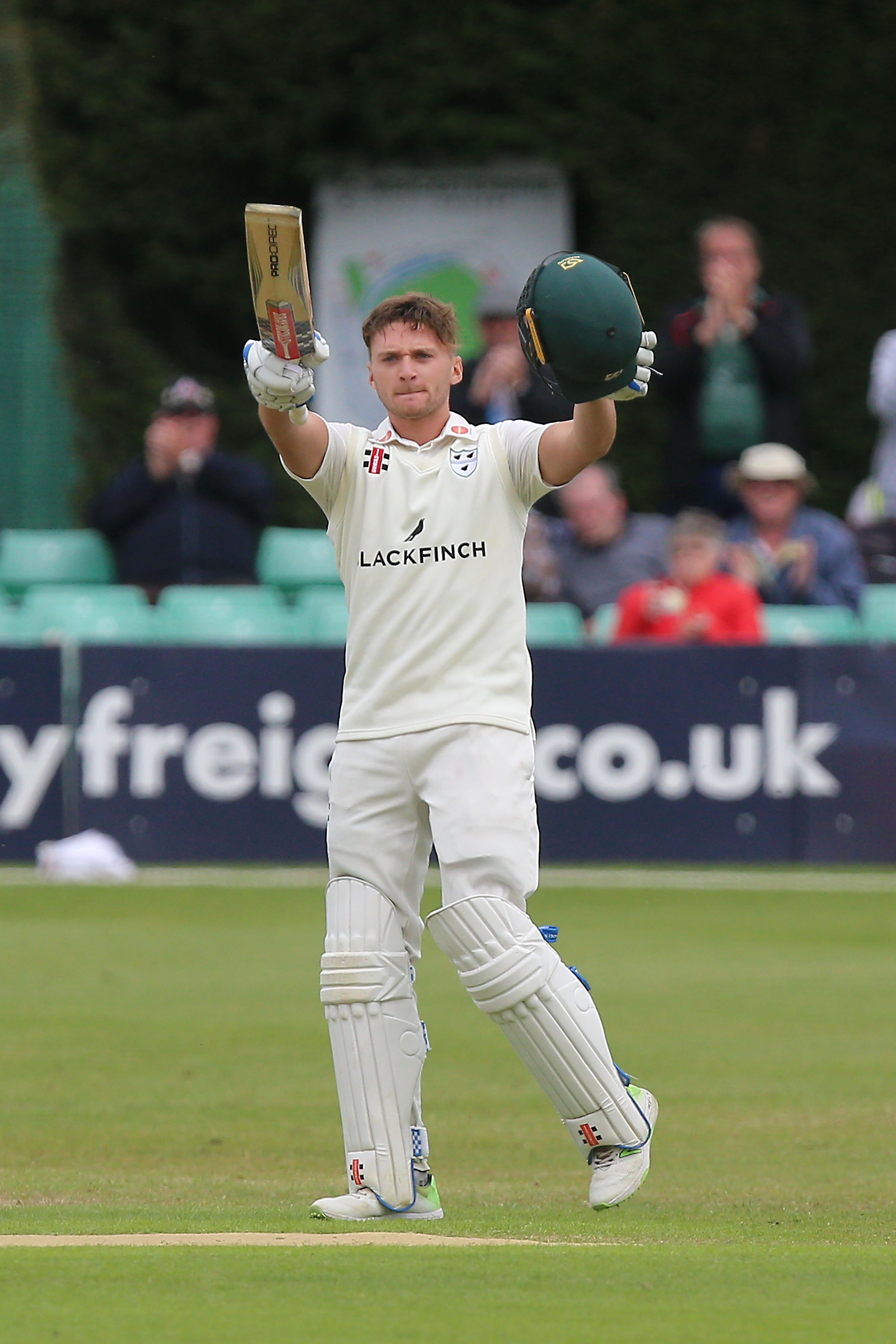 Great moment - Joe Clarke raises his bat following his century Picture: TGS PHOTO