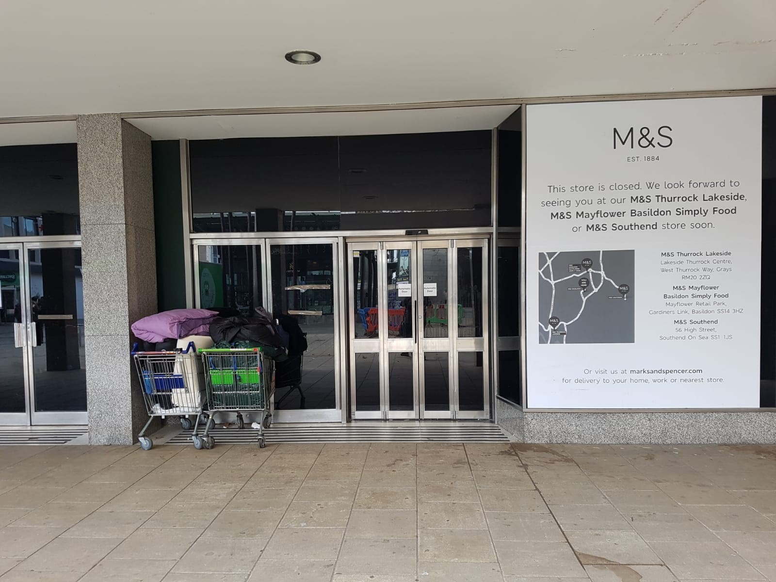 Broken in - the front of the former M&S store in Town Square, with trolleys carrying belongings outside