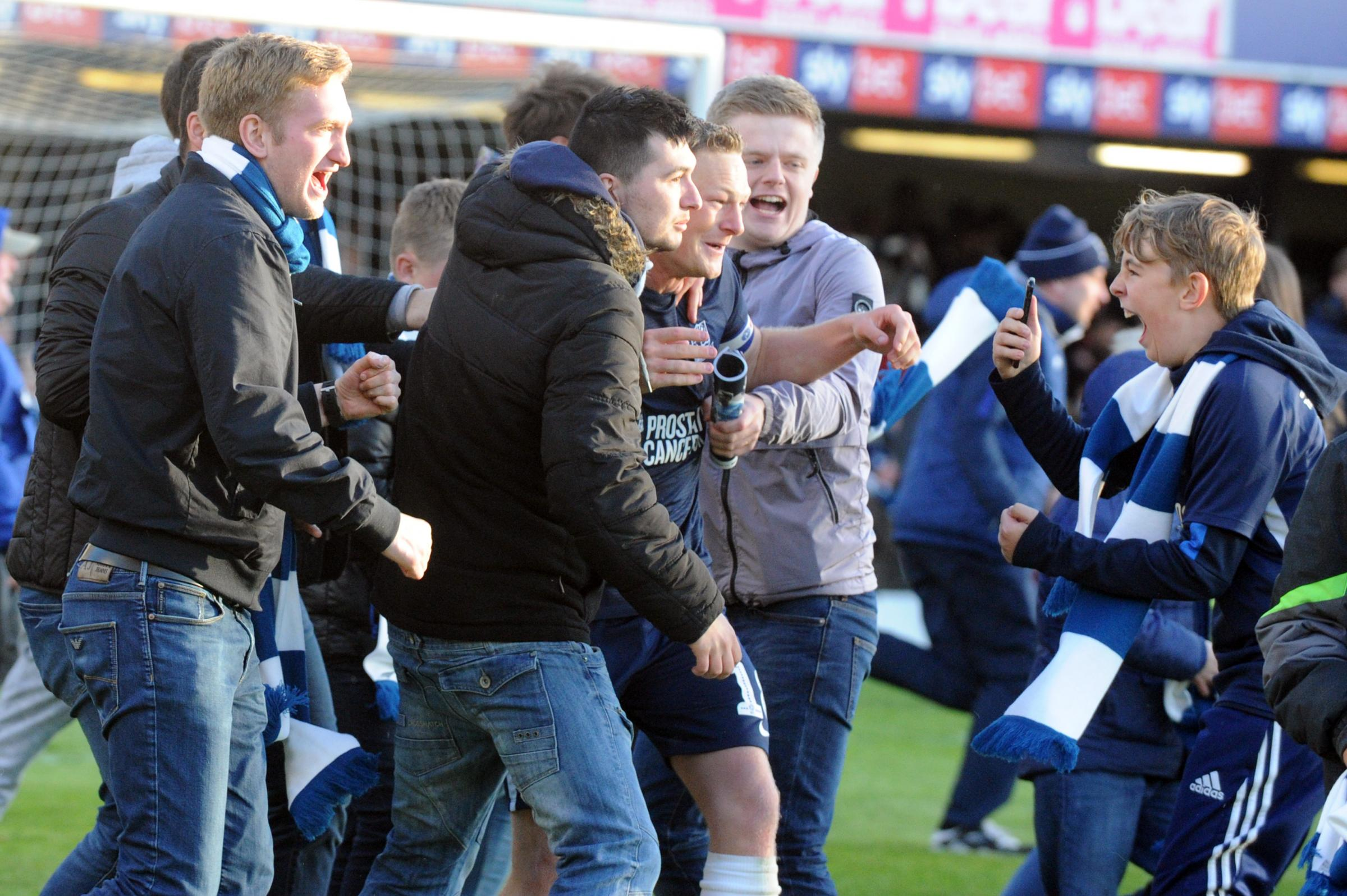 On the pitch - Southend United's fans celebrate on the pitch with skipper Sam Mantom